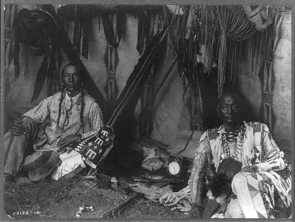 Image: Photograph of Little Plume and son Yellow Kidney sitting in a lodge. Taken by Edward Curtis in 1910. From the Library of Congress.